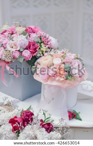 on a white table are boxes with a bouquet of roses and lilac