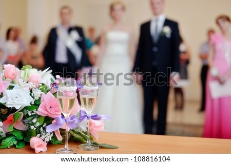 on a white table the wedding bouquet lies and nearby there are glasses - stock photo