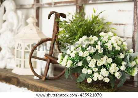 On a wooden board white flowers, lamps, toy bicycle. composition for gift cards - stock photo