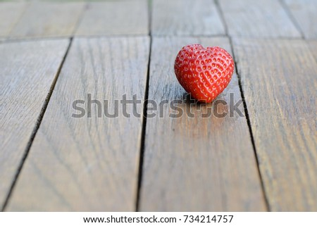 on a wooden brown table is a red strawberry