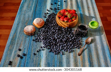 On a wooden kitchen table, laid out breakfast, two fresh muffins and fresh fruit, blueberry jam and black currant stands next in a glass - stock photo