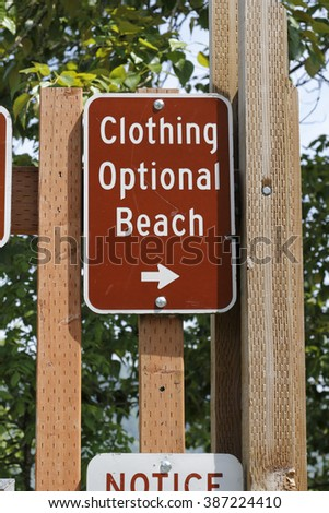 On a wooden post is a brown and white metal Clothing Optional Beach sign on wooden posts outside with foliage in the background on a sunny day.