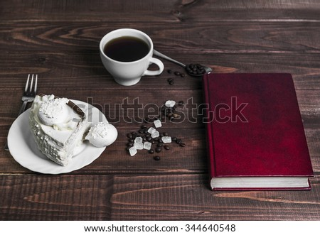 On a wooden table delicacy - a saucer with a piece of cake and a cup  meringue with coffee beans and sugar, the book in a red hard cover, fork, spoon, there is an empty space for your text or image - stock photo