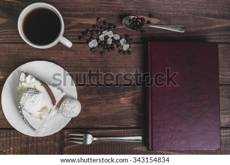 On a wooden table delicacy - a saucer with a piece of cake and a cup of meringue with coffee beans and sugar, the book in a red hard cover, fork, spoon, there is an empty space for your text or image - stock photo
