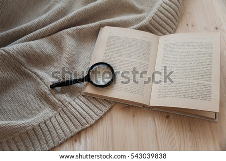on a wooden table lay an open book for reading and magnifying glass