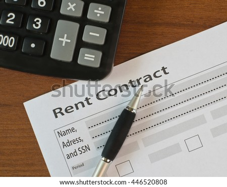 On a wooden table lies blank rent contract and pen