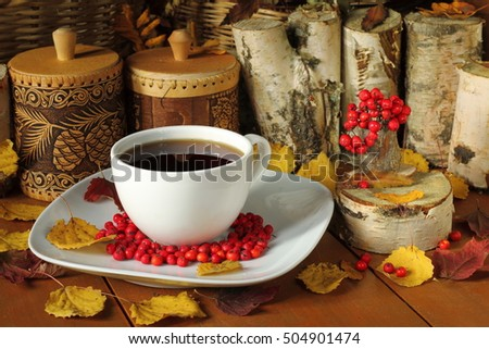 On a wooden table located a mug of tea, berries of mountain ash, autumn leaves and household items.