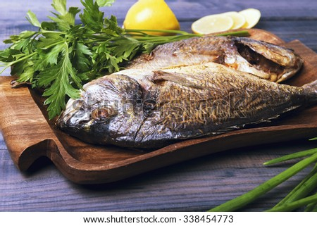On a wooden table plate with two roasted carp fish dorado with parsley, chives and lemon.
