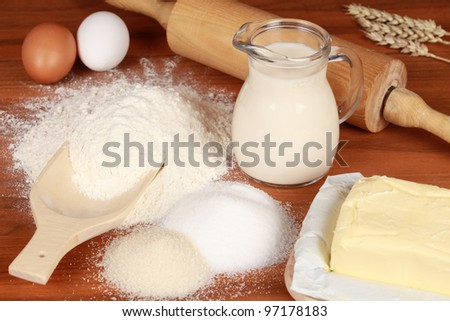On a wooden table there are ingredients for baking such as flour, sugar, eggs and milk