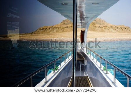 On aboard of the yacht. In the window of the yacht reflected sea shore of Sinai peninsula. Red Sea. Egypt.