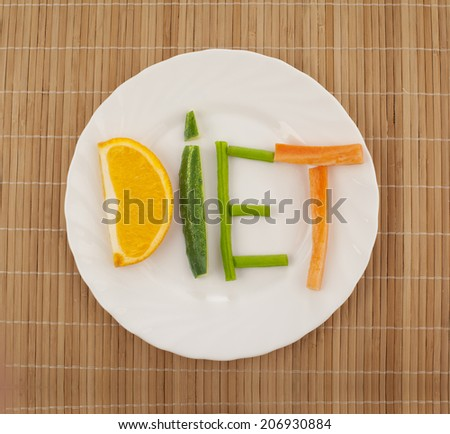 on bamboo or wooden table background is white plate with laid out on her word - diet - composed of slices of different fruits and vegetables - stock photo