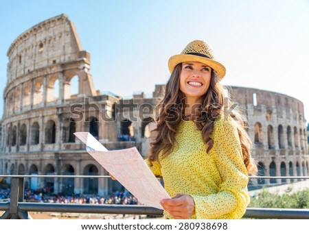 On beautiful summer's day, a woman is smiling and looking into the distance as she is holding a map of Rome. In the background, the Rome Colosseum and tourist crowds. - stock photo