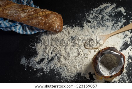 on black background bread with flour and towel