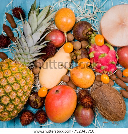 On blue wooden table background a composition made of fruits from Thailand. Coconut, pineapple, mango, rambutan, passion fruit, pithaya, papaya, kumquat, granadila