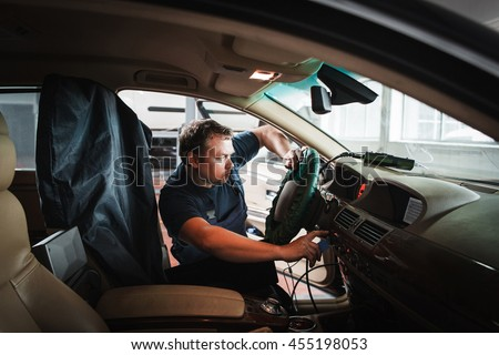On-board computer tuning by serviceman at garage. Professional electrician working with electronic part of car. Modern technologies in automobile