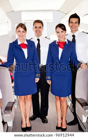 On board friendly team in an airplane smiling - stock photo