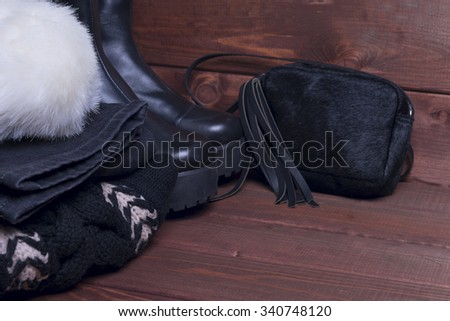 On brown wooden background winter black and white bow outfit for cold weather wool knitted sweater with a volume-neck collar, black jeans, small bag over shoulder, platform boots, fur bandage on head - stock photo