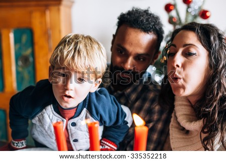 On Christmas Day, a child and a couple of friends have fun in play to blow to extinguish the candles placed on the table where there was the Christmas dinner. Behind them the decorated Christmas tree - stock photo