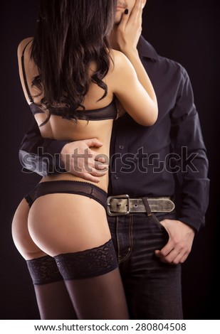 On dark background girl in lingerie with man in shirt