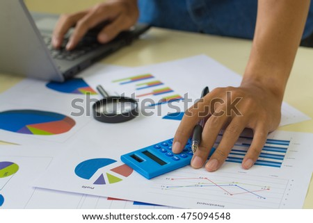 On desk, businessman use calculator and use laptop for work