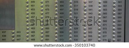 On-door metal speakerphone buttons in  house as  background. - stock photo