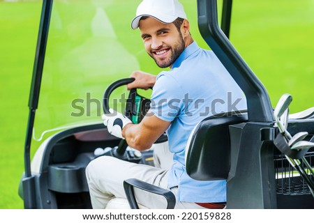 On his way to the next hole. Rear view of young happy male golfer driving a golf cart and looking over shoulder  - stock photo