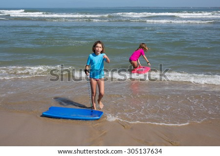 On holidays at the ocean, children have fun  surfing with bodyboard