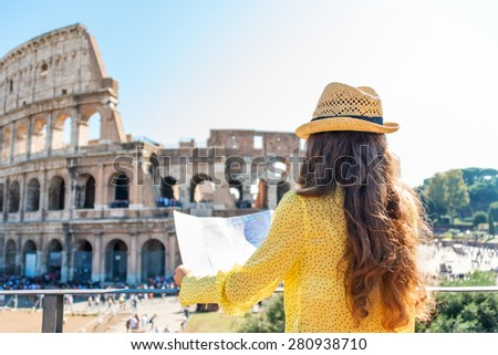 On hot summer's day, a woman is seen from behind and is holding a map of Rome. She is looking out onto Rome's Colosseum and the tourist crowds below. - stock photo