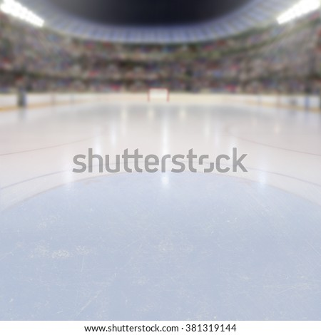 On ice low-angle view of a dramatic hockey arena full of fans in the stands with copy space. Deliberate focus on foreground ice and shallow depth of field on background with lighting flare effect. - stock photo