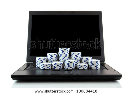 On-line gaming and gambling concept, laptop and white casino chips on keyboard - stock photo