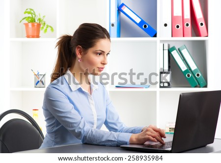On-line job. Young woman communicating with partners via internet. Confident sales person working at laptop in the office.  - stock photo