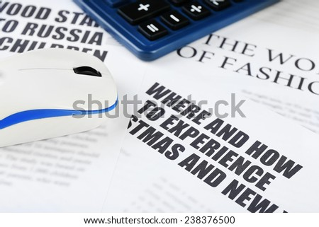 On-line news and business concept. Computer mouse, calculator and newspaper on wooden table background - stock photo