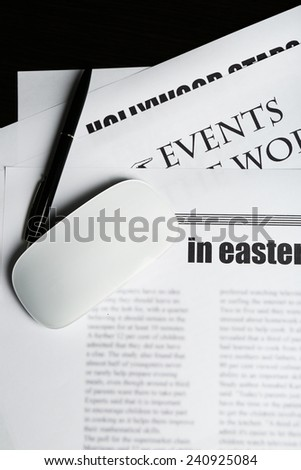 On-line news concept. Computer mouse and newspaper, close-up - stock photo