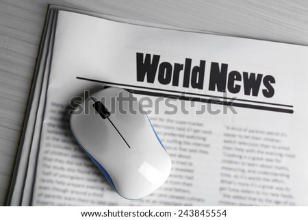 On-line news concept. Computer mouse and newspaper on wooden table background - stock photo