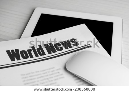 On-line news concept. Computer mouse, PC tablet and newspaper, close-up - stock photo