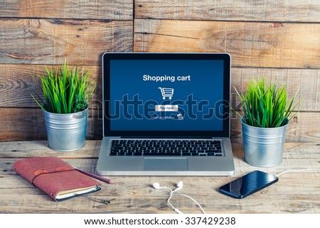 On line shopping. Cart in a laptop screen. - stock photo