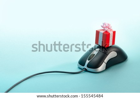On-line shopping. Gift box on top of computer mouse - stock photo