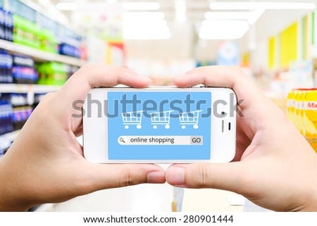 On line shopping on smart phone screen with blurred supermarket background, business, E-commerce, technology and digital marketing concept - stock photo