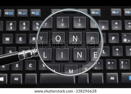 ON LINE written on keyboard with magnifying glass