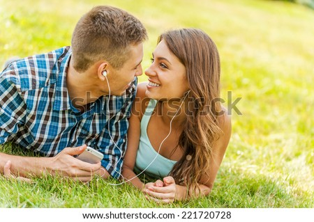 On one musical wave.  Young couple lying on the grass and listening to music together - stock photo