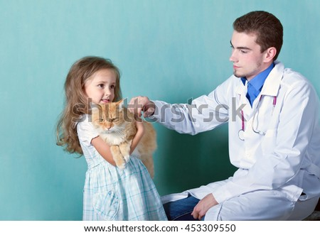 on reception at the the vet.little girl holding in her arms her cat, which she brought to the doctor - stock photo