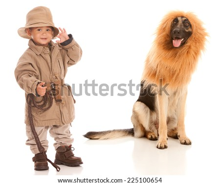 On safari.  Adorable toddler dressed in Khaki with a german shepherd dog wearing a lion's mane costume sitting behind him.  Isolated on white. - stock photo