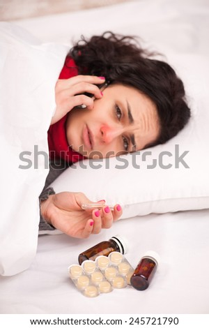 On sick leave. Young sick woman in thick scarf talking over the telephone and holding thermometer while lying in bed and having medicines and lozenges on the blanket - stock photo