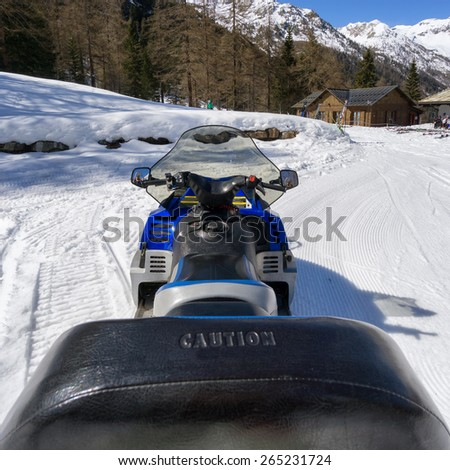 on snowmobile in high mountan with snow - stock photo
