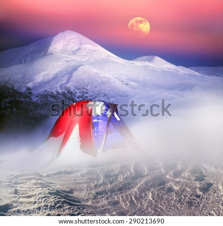On snowy mountain tops climbers and tourists, travelers establish modern tents in complex weather they protect and cherish their life and health, providing comfort and safety of the storm. - stock photo