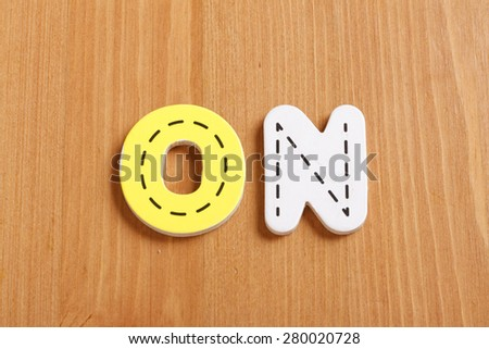ON, spell by woody puzzle letters with woody background - stock photo