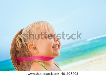 On sunny white sand beach happy smiling baby girl with vietnamese straw hat on head has fun before swimming in sea waves. Active travel family lifestyle, water activity on summer vacation with child. - stock photo