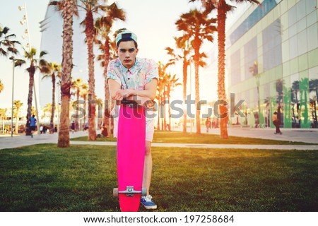 On the background of t palm trees young stylish man in bright summer clothes standing with a pink board with copy space - stock photo