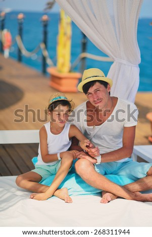 on the background of the sea under a canopy dad with a young son in a hat carrying on a conversation - stock photo
