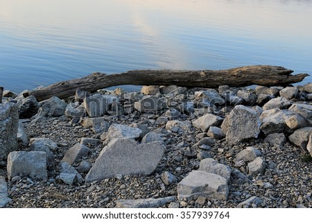 On the banks of Danube - Beautiful rocky sea shore with a driftwood tree trunk and Pile of rocks at sunrise or sunset on the banks of Danube Budapest, Hungary colours - stock photo